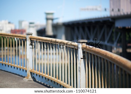 Curved steel railing with soft focus bridge and sky in Portland Oregon - stock photo