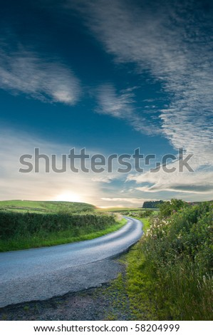Curved track leading to a summer sunset in Scotland - stock photo
