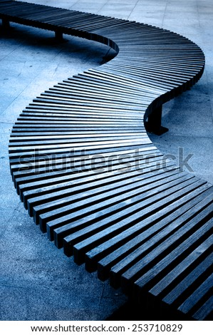Curved wooden boarded bench - stock photo