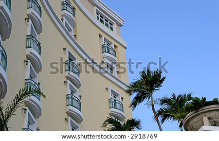 Curved yellow hotel against blue tropical sky
