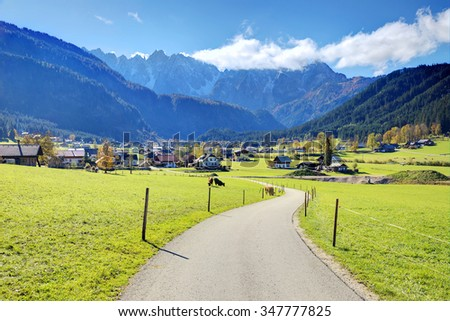 Curving country road through a green field under sunny sky with rugged mountains in the background ~ Idyllic autumn scenery of Gosau village in Austria - stock photo