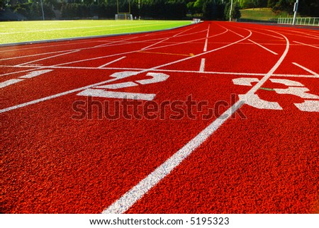 Curving lanes of a red race track and green football field - stock photo