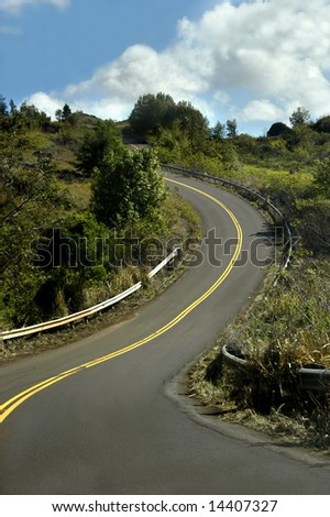Curving mountain road of Waimea Canyon State Park of the island of Kauai, Hawaii.  Road seems to curve into the sky. - stock photo