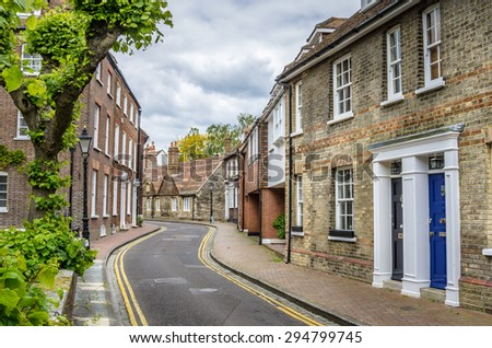 Curving Narrow Street and Terraced Houses on a Cloudy Day - stock photo