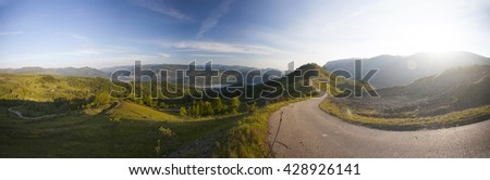 Curving road in the mountains in the sunrise - stock photo