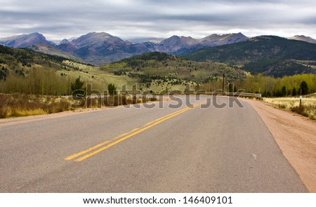 curving road pointing towards mountain peaks in the Pikes Peak region of Colorado, USA, Pikes Peak shrouded in the clouds