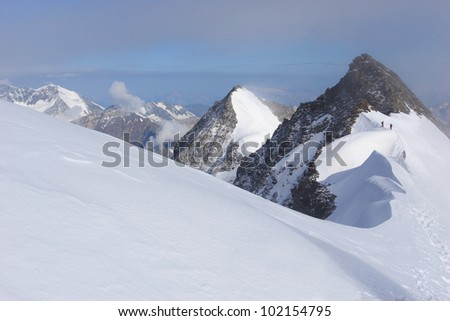 Curving snow ridge leads to rocky mountain summits with climbers. - stock photo