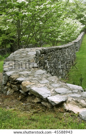 Curving Stone Wall with Blooming Dogwood Trees Vertical - stock photo