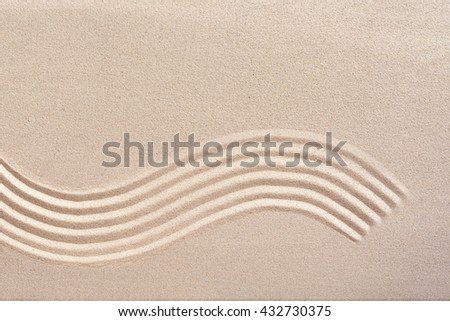 Curving wave pattern raked into smooth manicured sand in a Japanese zen garden for meditation and tranquility with copy space above - stock photo