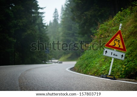 Curvy mountain road with slippery route sign - stock photo