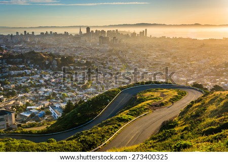 Curvy road and view of downtown at sunrise from Twin Peaks, in San Francisco, California. - stock photo