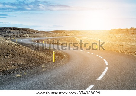 Curvy road in sunset - stock photo