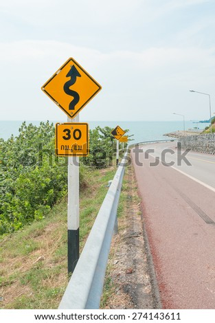 Curvy road sign down from hill - stock photo