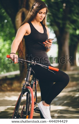 Curvy young woman texting leaning on fixie bicycle  - stock photo