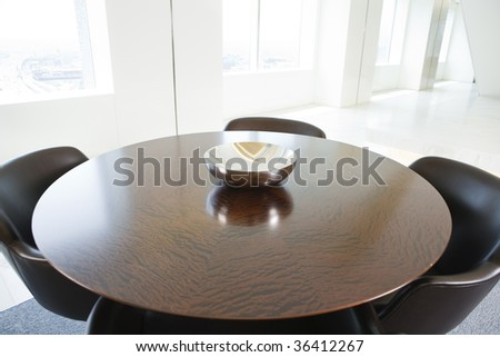 cushioned chairs at wood conference table.