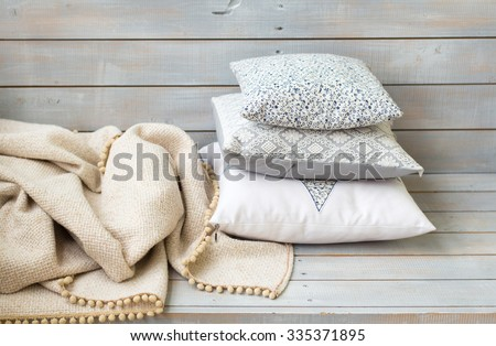 Cushions and plaid on the white wooden background closeup. - stock photo