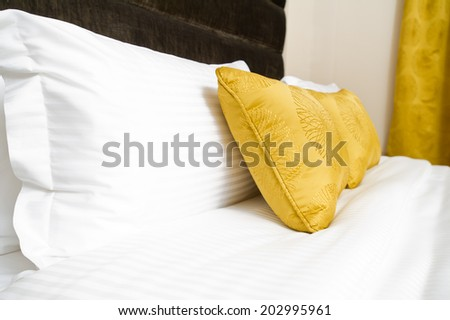 Cushions , Yellow pillows on bed  - stock photo