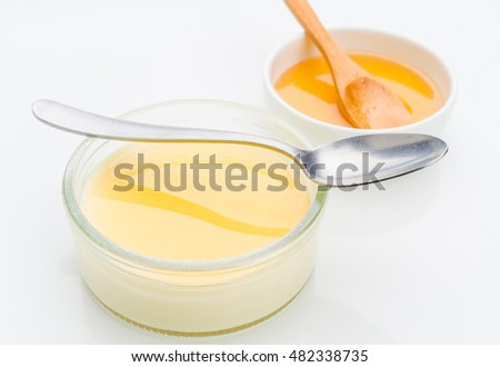 custard with honey in small glass jar isolated on white