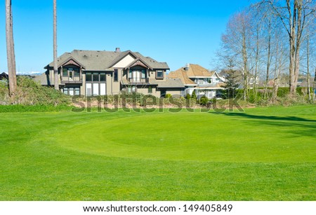 Custom built big luxury house with nicely trimmed front yard, lawn in front of the golf course in a residential neighborhood. Vancouver Canada. - stock photo
