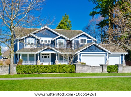 Custom built big luxury house with triple garage doors in a residential neighborhood. Suburbs of Vancouver ( Surrey ) Canada. - stock photo