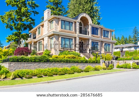 Custom built luxury contemporary house with nicely trimmed and landscaped front yard lawn and driveway to garage in a residential neighborhood. Vancouver Canada. - stock photo