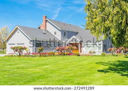 Custom built luxury farm house with nicely trimmed and designed front yard, tulips, lawn in a residential neighborhood in Canada. Large family house. - stock photo