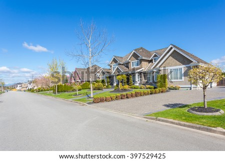 Custom built luxury homes with nicely trimmed and designed front yard, lawn in a residential neighbourhood in Canada. Street of houses. - stock photo