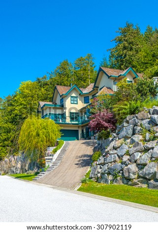 Custom built luxury house  on the hill with nicely trimmed front yard, lawn and paved driveway in a residential neighborhood. Vancouver Canada. - stock photo