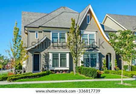 Custom built luxury house, townhouse, duplex with nicely trimmed front yard, lawn in a residential neighborhood. Vancouver Canada. - stock photo