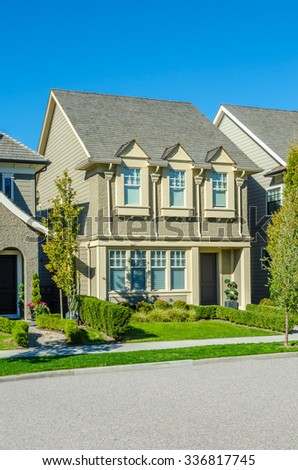 Custom built luxury house, townhouse with nicely trimmed front yard, lawn in a residential neighborhood. Vancouver Canada. Vertical. - stock photo