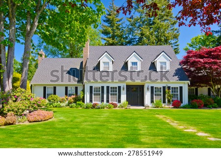 Custom built luxury house with nicely trimmed and decorated front yard, lawn in a residential neighborhood. Vancouver Canada. - stock photo