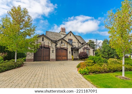 custom built luxury house with nicely trimmed and designed front yard lawn in a residential