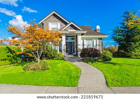 Custom built luxury house with nicely trimmed and designed front yard, lawn in a residential neighbourhood in Canada. Beautiful fall tree with yellow leaves, blue sky, sunny day. - stock photo