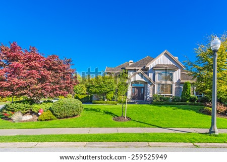 Custom built luxury house with nicely trimmed and designed front yard, lawn in a residential neighbourhood in Canada. - stock photo