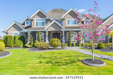 Custom built luxury house with nicely trimmed and designed front yard, lawn in a residential neighbourhood in Canada. Magnolia blossoms. - stock photo