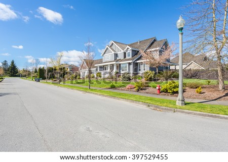 Custom built luxury house with nicely trimmed and designed front yard, lawn in a residential neighbourhood in Canada. Street of houses.