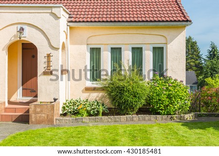Custom built luxury house with nicely trimmed and designed front yard, lawn in a residential neighbourhood in Canada. Fragment of the porch and front window. - stock photo