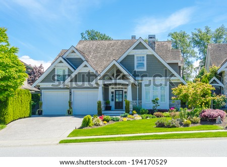 Custom built luxury house with nicely trimmed and landscaped front yard and driveway to double doors garage in residential neigborhood. Vancouver, Canada. - stock photo