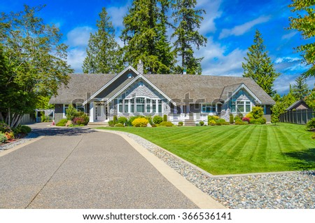 Custom built luxury house with nicely trimmed and landscaped front yard, lawn and driveway in a residential neighborhood. Vancouver Canada. - stock photo