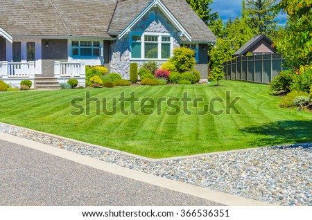 Custom built luxury house with nicely trimmed and landscaped front yard, lawn and driveway in a residential neighborhood. Vancouver Canada. Vertical. - stock photo