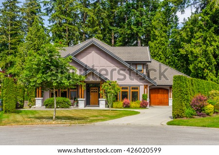 Custom built luxury house, with nicely trimmed and landscaped front yard, lawn and driveway to garage in a residential neighborhood. Vancouver Canada. - stock photo