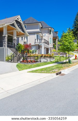 Custom built luxury house with nicely trimmed and landscaped front yard lawn and driveway to garage in a residential neighbourhood. Vancouver Canada.
