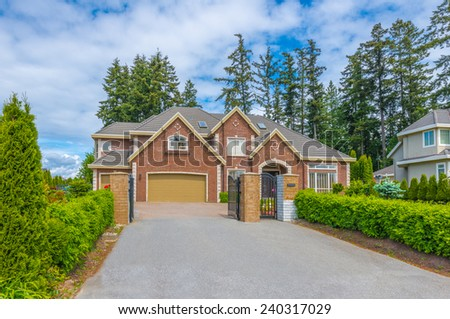 Custom built luxury house with nicely trimmed and landscaped front yard, lawn and wide driveway to the garage in a residential neighborhood. Vancouver Canada. - stock photo