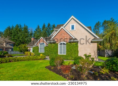 Custom built luxury house with nicely trimmed and landscaped front yard lawn in a residential neighborhood. Vancouver Canada.