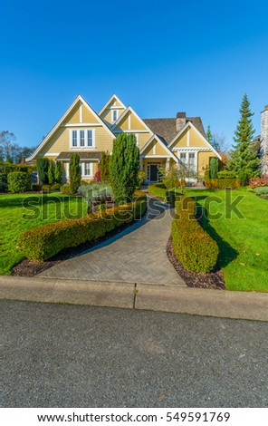 Custom built luxury house with nicely trimmed and landscaped front yard lawn  in a residential neighborhood. Vancouver, Canada.