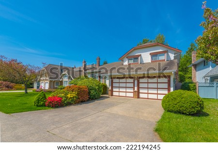 Custom built luxury house with nicely trimmed front yard, and driveway to the double doors garage in a residential neighborhood. Vancouver. Canada. - stock photo