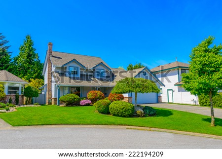Custom built luxury house with nicely trimmed front yard, in a residential neighborhood. Vancouver Canada. - stock photo
