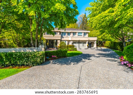 Custom built luxury house with nicely trimmed front yard, lawn and driveway to garage in a residential neighborhood. Vancouver. Canada. - stock photo