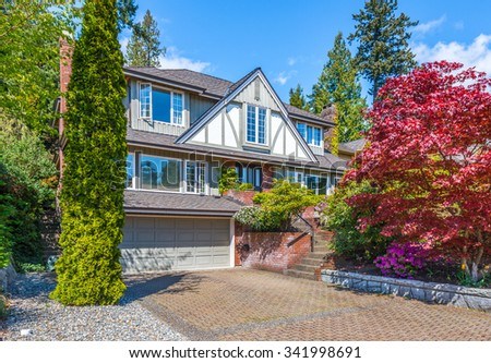 Custom built luxury house with nicely trimmed front yard, lawn and driveway to garage in a residential neighborhood. Vancouver Canada.