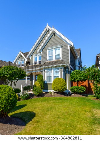 Custom built luxury house with nicely trimmed front yard, lawn and driveway to garage in a residential neighborhood. Vancouver Canada. - stock photo
